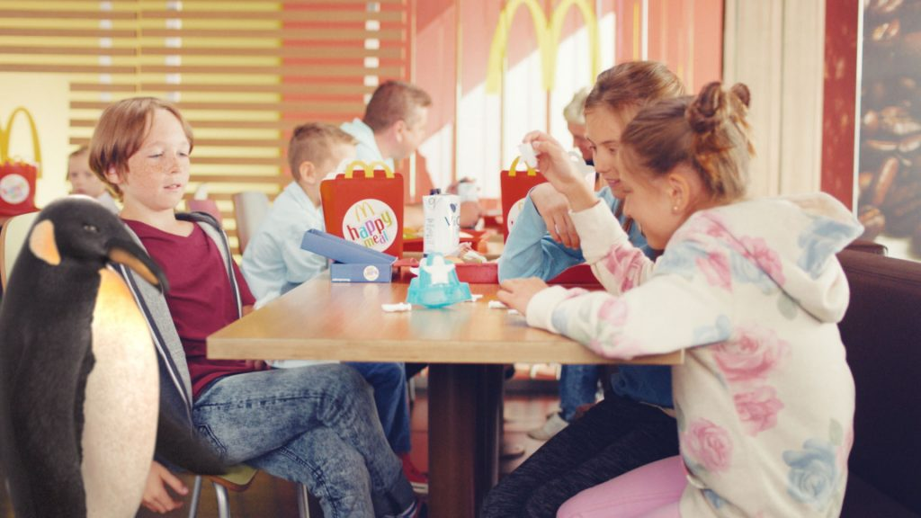 A group of kids sitting in a McDonalds restaurant playing with their happy meal toys next to our VFX-penguin.