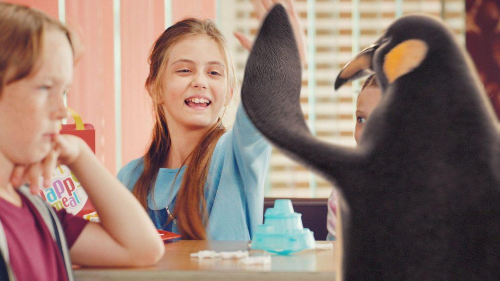 "A smiling girl giving our McDonald's VFX penguin ""high-five""."