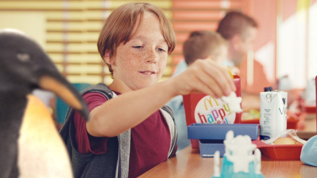 A boy sitting at a table playing with his McDonald's happy-meal toy while our VFX-penguin stands next to him.