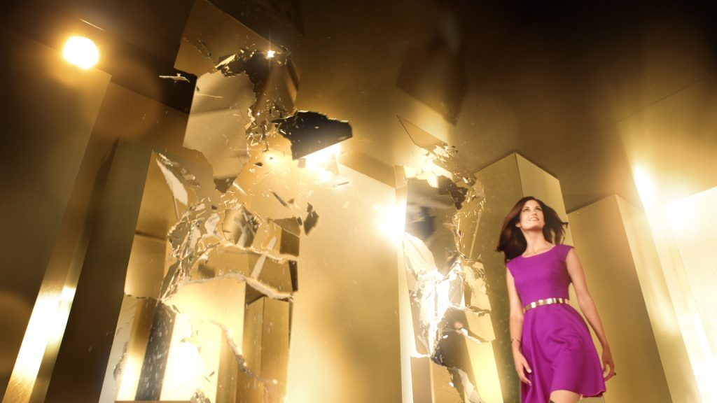 A woman in a purple wool dress walking through a bright golden VFX rendered room with lots of shattering mirrors.