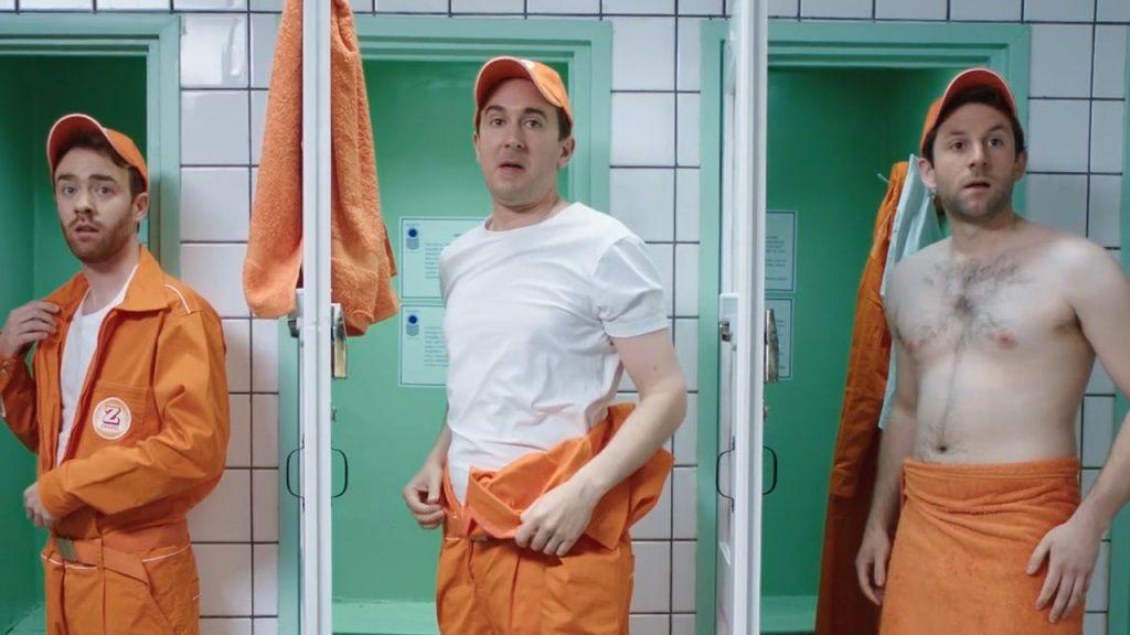 """Three men in orange Zweifel """"Cractive"""" overalls changing in front of green lockers."""