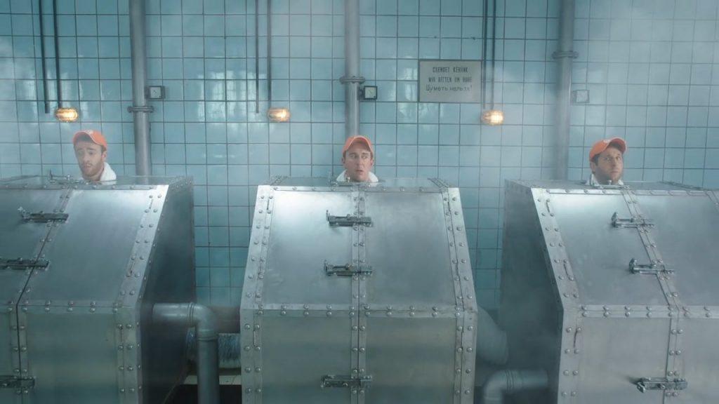 "Three men wearing orange Zweifel ""Cractiv"" baseball caps steaming in russian metal-saunas."