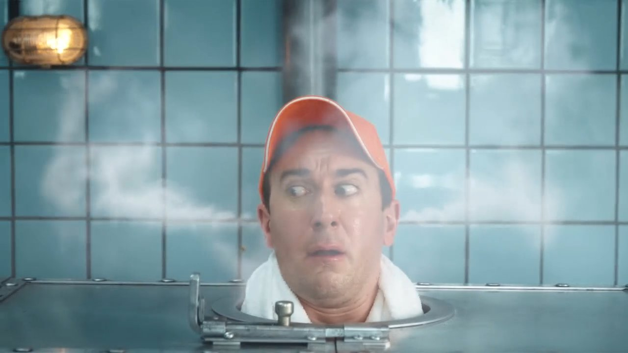 Another man wearing an orange Zweifel baseball cap in a russian metal-sauna with VFX-steam coming out of his ears.