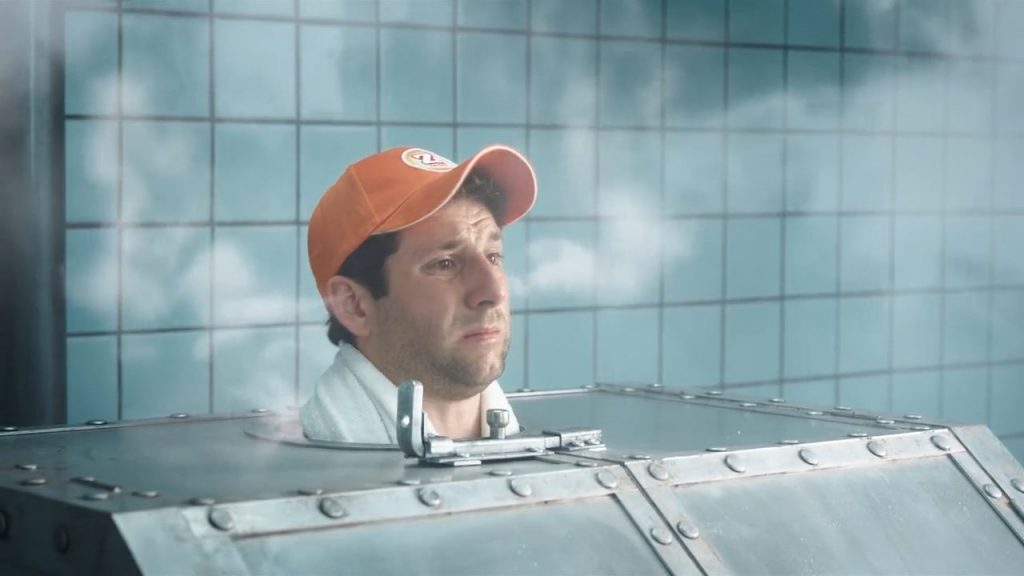 """A man wearing an orange Zweifel """"Cractive"""" baseball cap in a russian metal-sauna with VFX-steam coming out of his ears."""