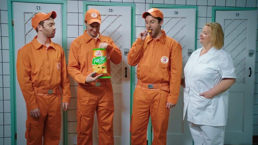 """Three men in orange overalls standing beside a stout, blonde nurse in white uniform, enjoying some Zweifel """"Cractiv"""" potato-chips."""