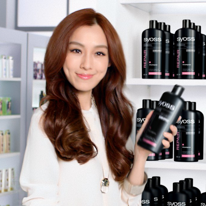 A japanes women in a drugstore happily holding a black Syoss Creatin shampoo bottle which was added using VFX.